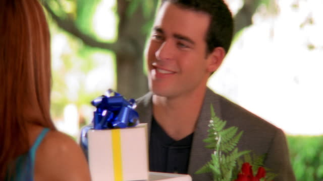 close up tilt up rear view man giving gifts + flowers to woman standing in doorway - war in afghanistan: 2001 present stock-videos und b-roll-filmmaterial
