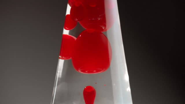 vídeos y material grabado en eventos de stock de close up tilt up red blobs collecting in clear fluid at top of lava lamp - electric lamp
