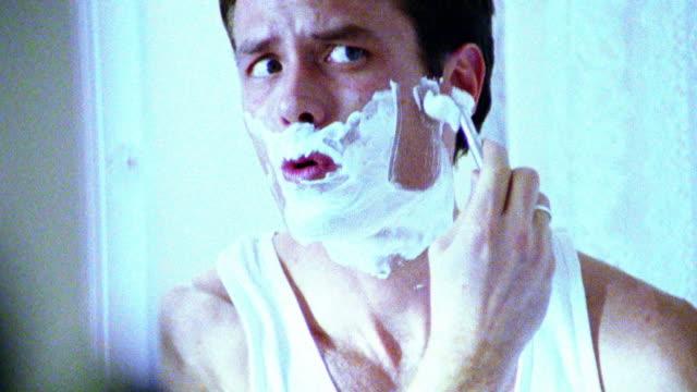 vídeos de stock, filmes e b-roll de blue overexposed close up tilt up reflection in mirror of man shaving with razor in bathroom - superexposto