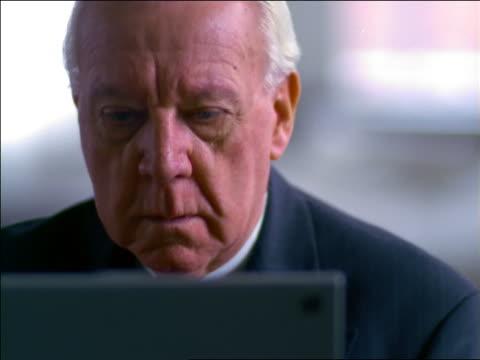 vídeos de stock, filmes e b-roll de close up tilt up senior businessman typing on laptop computer + nodding / starts to smile - só um homem idoso