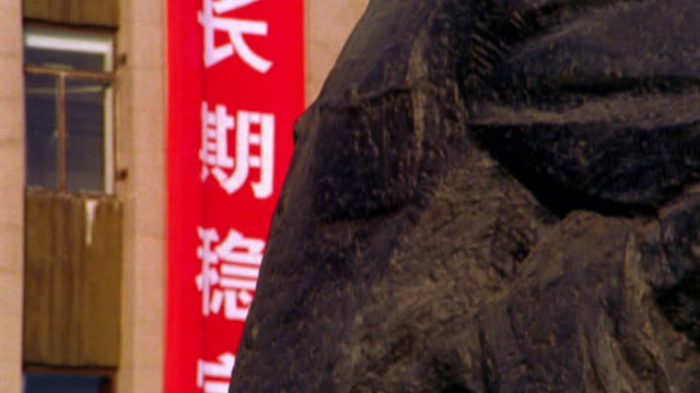 close up tilt up statue of Mao Zedong with Chinese writing on banner in background / The Bund, Shanghai, China