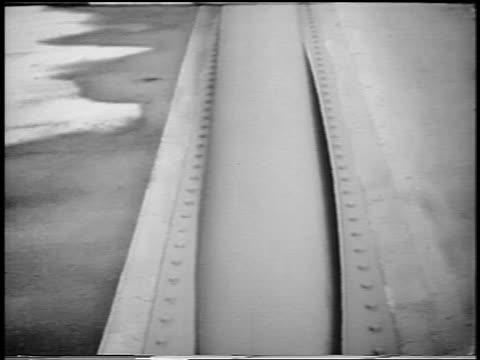 B/W 1940 close up tilt up suspension bridge cable blowing in wind / TacomaNarrows Bridge collapse WA / news
