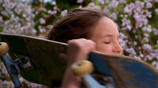 Close up tilt up teenage girl holding skateboard on shoulders / posing