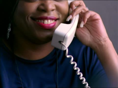 vídeos y material grabado en eventos de stock de close up tilt up + tilt down black woman sitting by window talking on telephone + smiling - teléfono con cable