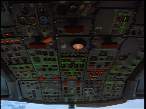 close up tilt up + tilt down ceiling of airliner cockpit with hands of male pilot + co-pilot hitting controls / toronto - 飛行士点の映像素材/bロール