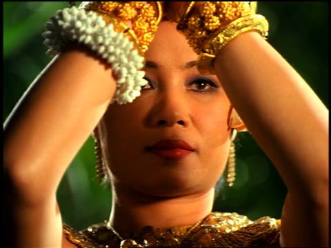 """close up tilt up tilt down face + hands of cambodian woman in native dress doing native dance in """"jungle"""" - 女性ダンサー点の映像素材/bロール"""