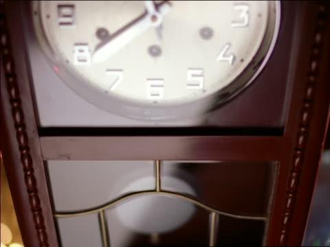 close up tilt up tilt down pendulum clock swinging - 大時計点の映像素材/bロール