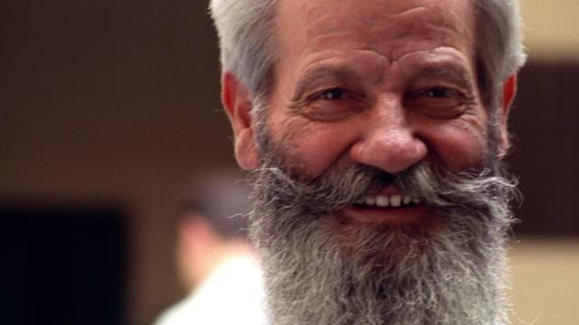close up tilt up tilt down PORTRAIT bearded Italian senior man smiling outdoors / Italy