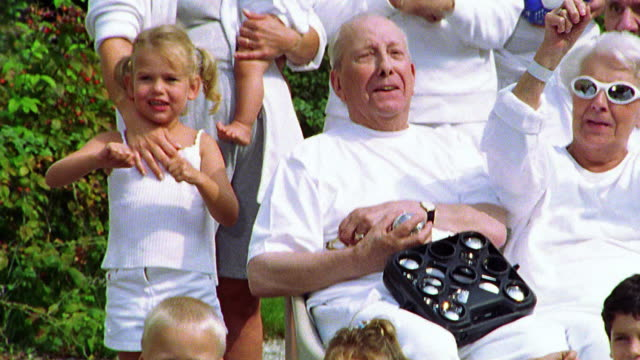 close up tilt up tilt down pan portrait multi-generational group holding sports equipment lifting arms in celebration - tennis racket stock videos & royalty-free footage