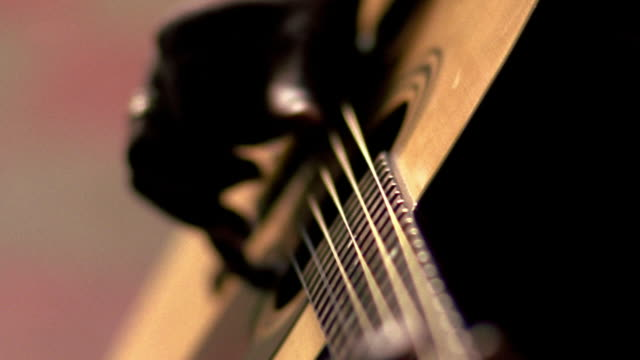 close up tilt up tilt down rack focus from hands to face of black man playing guitar indoors / nova scotia, canada - soft focus stock videos & royalty-free footage
