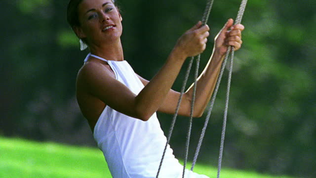 stockvideo's en b-roll-footage met close up tilt up tilt down pan woman in white dress swinging on tree swing outdoors - witte jurk