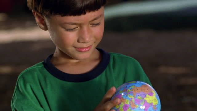 close up tilt up tilt down young asian boy examining small globe + holding it up to camera outdoors - 地図点の映像素材/bロール