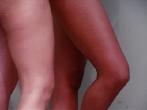 1969 close up tilt up two women's legs in bikinis standing against wall / hawaii / travelogue - ワンピース型の水着点の映像素材/bロール