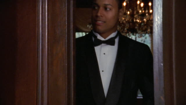 close up tilt up waiter wearing tuxedo opening double doors / looking at cam and smiling - tuxedo stock videos and b-roll footage