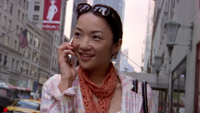 stockvideo's en b-roll-footage met close up tilt up woman talking on mobile phone and walking down city street / new york city - 2004