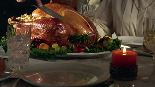 Close up tilt up zoom in hands of man carving roast turkey on platter on dining room table