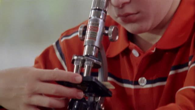 vidéos et rushes de close up tilt up zoom out medium shot boy focusing microscope - regarder à travers