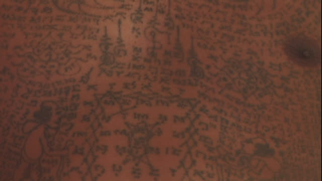 close up tilt-down - a man bears tattoos that depict magic spells. / thailand - navel stock videos & royalty-free footage