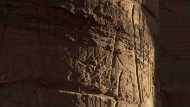 Close Up, tilt-up - A close-up view shows carvings of hieroglyphs on the column of an old Egyptian adobe building / Egypt