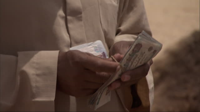 close up, tilt-up - an egyptian man counts money - egypt stock videos & royalty-free footage