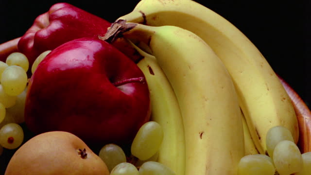 close up time lapse bananas, apples, pear and grapes ripening + beginning to rot in front of black background - decay stock videos & royalty-free footage