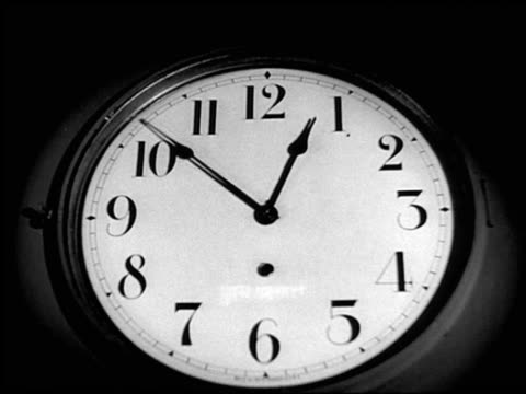 b/w close up time lapse clock emerging from shadows - orologio video stock e b–roll