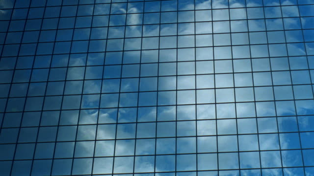 close up time lapse clouds + storm clouds reflected in windows of Houston office building / Texas