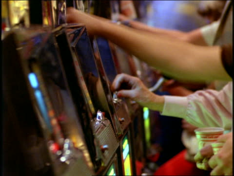 close up time lapse hands of line of people playing slot machines in casino / Las Vegas, Nevada