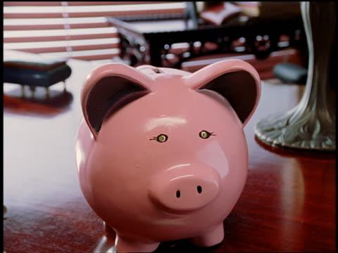 vidéos et rushes de close up time lapse male hands putting coins in pink piggy bank - tirelire