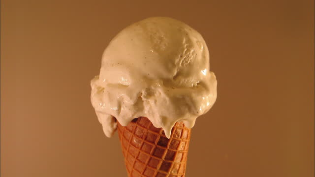 close up time lapse melting vanilla ice cream cone - eis stock-videos und b-roll-filmmaterial