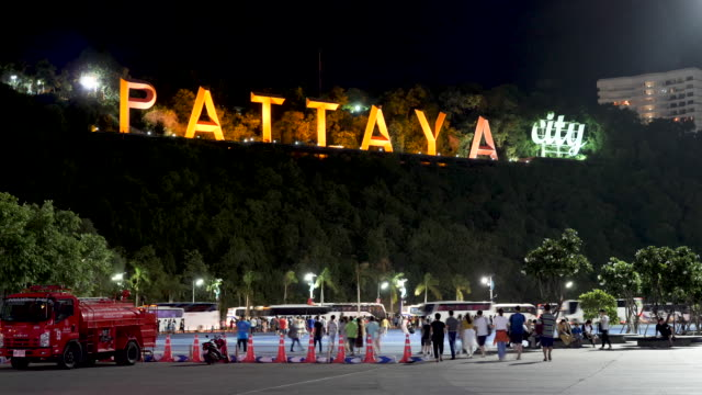 4k t/l close up time lapse of the famous pattaya sign in thailand. scene shows tour groups walking to the bus terminal to get bus and coaches to their hotels. - pattaya stock videos & royalty-free footage