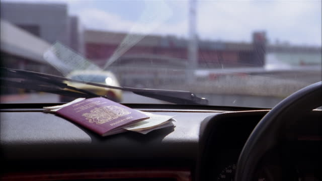 Close up time lapse passport on dashboard of car driving to airport terminal
