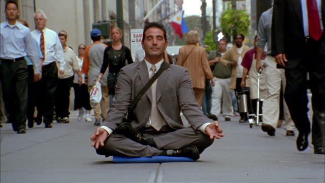 close up time lapse pedestrians walking / businessman sitting in lotus position on sidewalk - 心の平穏点の映像素材/bロール
