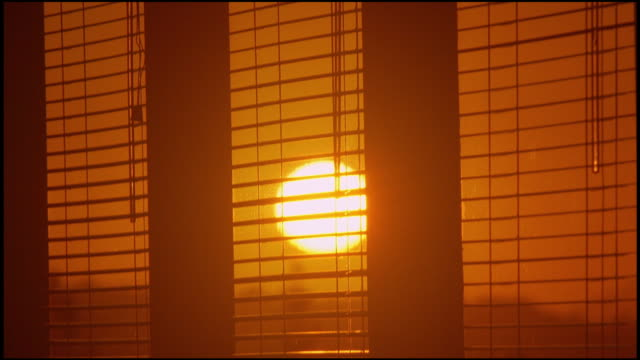 close up time lapse sun setting through blinds in office window - jalousie stock-videos und b-roll-filmmaterial