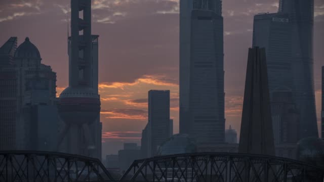 Close up timelapse of sunrise over Waibaidu Bridge silhouetting the Oriental Pearl Tower and other buildings in the financial center of Lujiazui in...