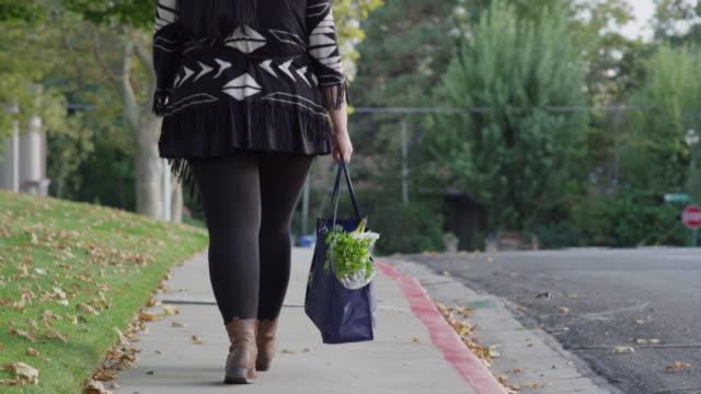 close up to medium shot of woman carrying groceries on sidewalk / orem, utah, united states - orem bildbanksvideor och videomaterial från bakom kulisserna