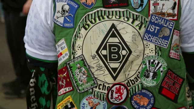 vídeos y material grabado en eventos de stock de close up to mid shot of borussia fan with multiple club badges on his back vfl borussia moenchengladbach v fc augsburg bundesliga editorial video... - insignia accesorio personal