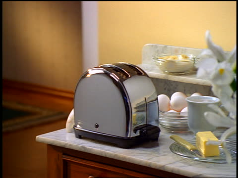 close up toast popping up in toaster on kitchen counter with eggs + butter - toaster appliance stock videos & royalty-free footage