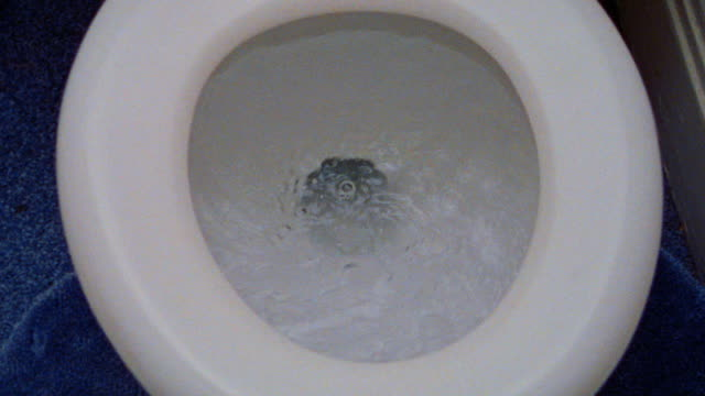 stockvideo's en b-roll-footage met overhead close up toilet flushing in bathroom - badkamer