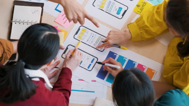 close up top view asian ux developer and ui designer hand brainstorming about mobile app interface wireframe design on table color code at modern office.creative digital development agency - prototype stock videos & royalty-free footage