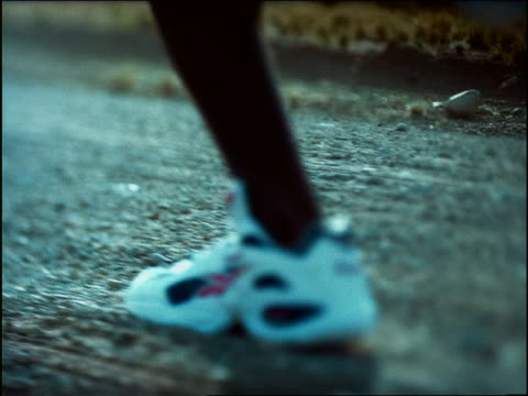 OVEREXPOSED FAST close up tracking shot Black male athlete's feet running in desert / tilt up to silhouette of legs