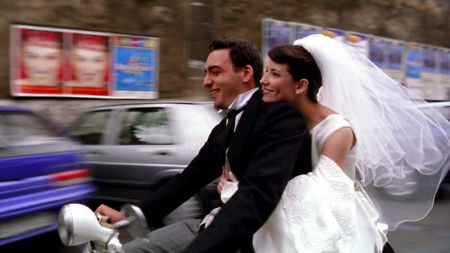 close up tracking shot bride kissing groom while riding scooter on city street / Rome, Italy