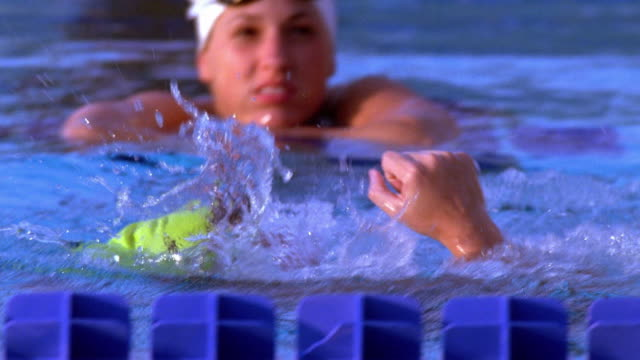 vídeos de stock e filmes b-roll de close up tracking shot female swimmer celebrating victory in pool / california - gesticular