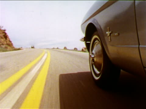 vídeos de stock, filmes e b-roll de 1965 close up tracking shot front wheel + fender of moving ford mustang on country road / industrial - 1965