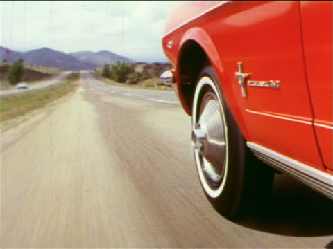 1965 close up tracking shot front wheel + fender of moving red ford mustang on country road / industrial - ford mustang stock videos and b-roll footage