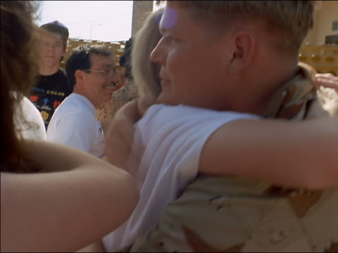 close up tracking shot gulf war soldier hugging people upon return home - homecoming stock videos & royalty-free footage