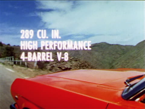 1965 close up tracking shot hood of red Ford Mustang driving on mountain road / industrial