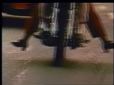 1970 close up tracking shot legs of couple riding motorcycle in traffic on street / woman's legs sticking out - beliebiger ort stock-videos und b-roll-filmmaterial
