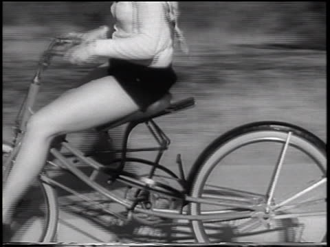 vídeos y material grabado en eventos de stock de b/w 1933 close up tracking shot legs of woman riding on bouncing bicycle on road / san francisco, california / newsreel - bicicleta vintage