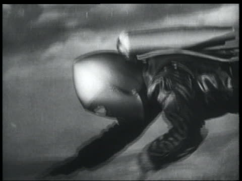 b/w 1952 close up tracking shot man in jet pack + helmet descending in air - 1952 stock videos & royalty-free footage